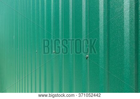 Galvanized Iron Fence With Corrugated Vertical Stripes Closeup Of Texture Of Green Roofing Of Sheet