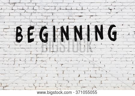 Word Beginning Written With Black Paint On White Brick Wall.
