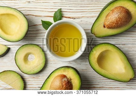 Ripe Fresh Avocado And Oil On White Wooden Background, Top View