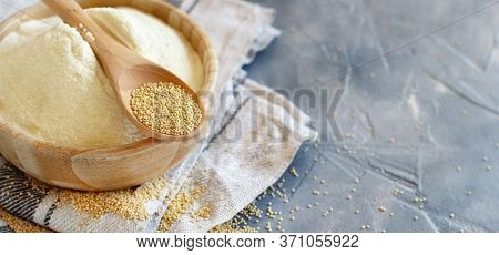 Bowl Of Raw Amaranth Flour With A Spoon Of Amaranth Seeds On A Grey Table Close Up