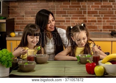 Cheerful Mother And Two Daughters Are Eating Healthy Salad Together At Home. The Concept Of Healthy
