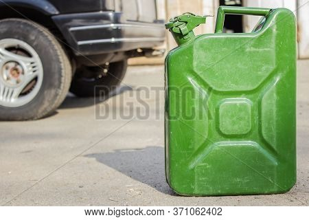 Green Jerry Can Close-up On Blurred Background Of Black Car. Copy Space For Your Text