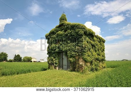 An Old Ivy-covered Church In Countryside In A Summer Day Against A Blue Sky With Some Clouds - Conce
