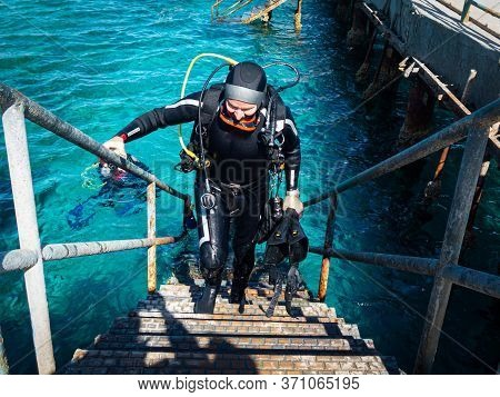 A Male Scuba Diver, 50+, Climb Up The Stairs To The Jetty Returning From  A Scuba Dive With Heavy Eq