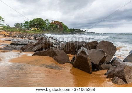 Beach With Red Sand And Red Rocks With A Dramatic Sky In Congo Town, Monrovia, Liberia