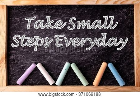 Chalkboard And Color Chalks With Text Take Small Steps Everyday. Inspirational Quotes And Business M