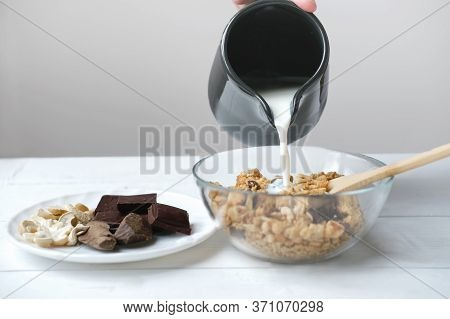 Homemade Granola With Chocolate And Nuts. Granola In A Transparent Bowl With Pouring Milk And Chocol
