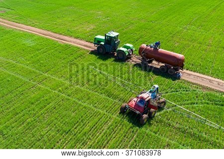 Tractor Field Treatment With Herbicides. The Farmer Pours A Chemical Into The Sprayer. Next To It Is