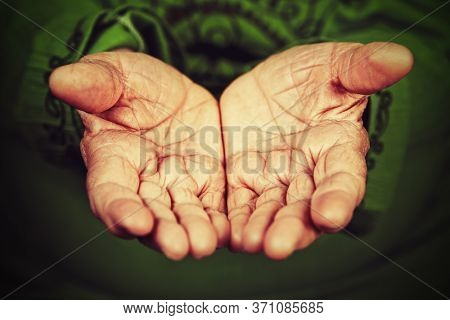 Old wrinkled lady hands with open palms. Begging, help or elderly people care concept