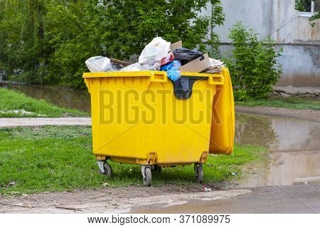 Trash Cans Are Full. Yellow Trash Bin, Plastic Trash Can, Solid Waste.