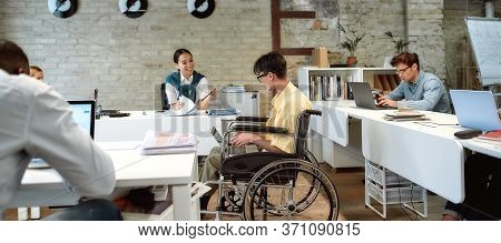 Portrait Of Young Male Office Worker In A Wheelchair Talking To Female Colleague While Using Laptop
