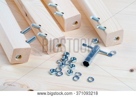 Bolts And Nuts For The Assembly Of Wooden Furniture. Four Legs From The Cradle