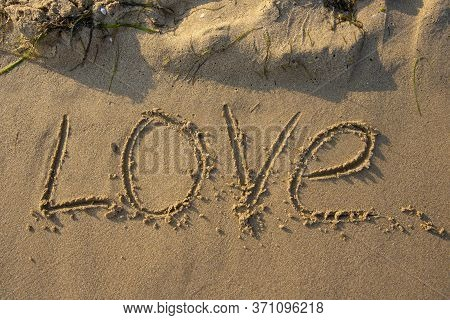 The Word Love Written By Hand In The Sand.
