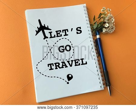 In A White Notebook A Plane Is Drawn And Written Let's Go Travel. Image For Travel Agency. The Conce