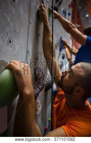 Close up of male trainer climbing wall in health club