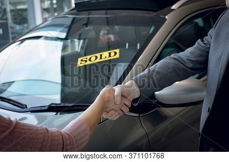Cropped image of salesman doing handshake with customer while standing by car in showroom