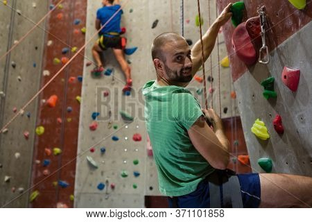 Portrait of male athlete climbing wall in health club