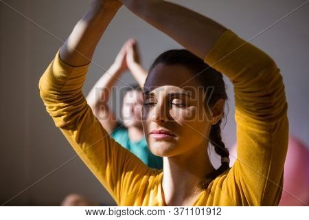 Woman meditating in prayer position at health club