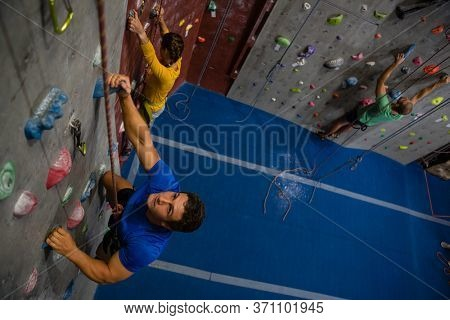 High angle view of confident athletes climbing wall in health club