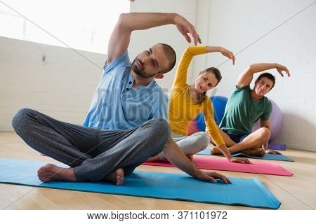 Male instructor with students exercising at yoga studio