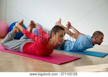 Female student practicing bow pose with instructor in yoga studio