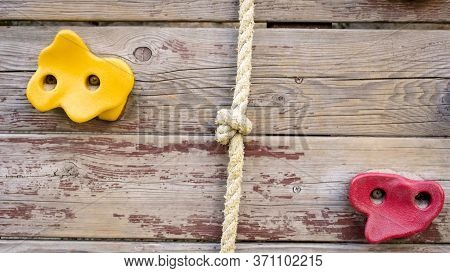Colorful Plastic Grips And Ropes On Wall At Cliff Climbing Center