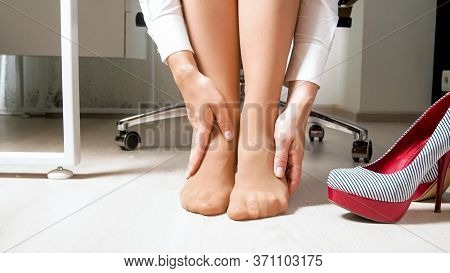 Yougn Woman Feeling Pain In Legs And Feet After Hard Working Day In Office