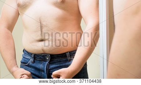 Fat Young Man With Big Belly Pretending To Be Muscular And Fit. Concept Of Male Overweight, Weight L