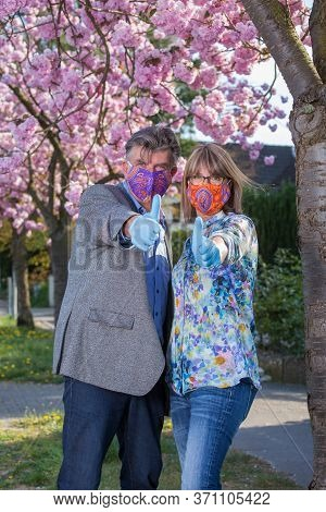 Senior Couple In Face Masks Giving A Thumbs Up.