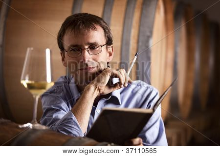 Smiling winemaker in cellar looking satisfied at a glass of white wine with notebook and pen in hands.