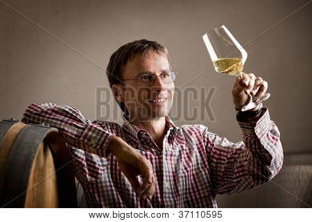 Smiling winemaker looking at glass of white wine for quality testing, leaning on barrel in wine cellar.