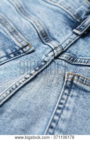 Close-up Of Denim Blue Fabric With Pockets And Yellow Seams. Fashionable Jeans. Front View.