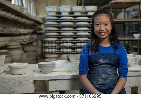 Portrait of happy girl standing near worktop in pottery workshop