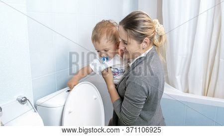 Little Toddler Boy Flushing Water In Toilet With Young Mother