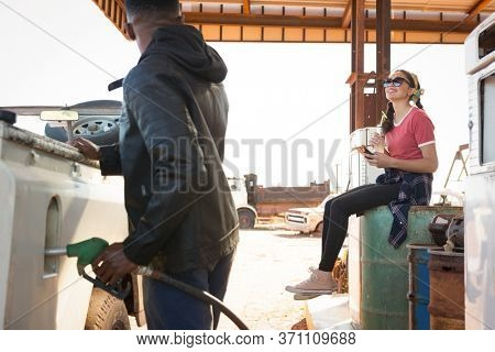 Man filling petrol in car while woman sitting at petrol pump station on a sunny day