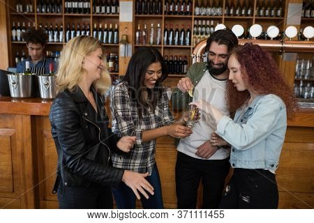 Happy friends having tequila shot at counter in bar