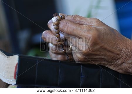 Hands Of Asia Senior Woman Holding Rosary On Bible Book. A Spiritual Grandmother Praying Rosary Clos