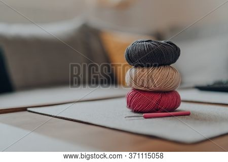 Stack Of Few Different Coloured Balls Of Dk Wool Yarn On A Wooden Table, Crochet Hook Near, Shallow