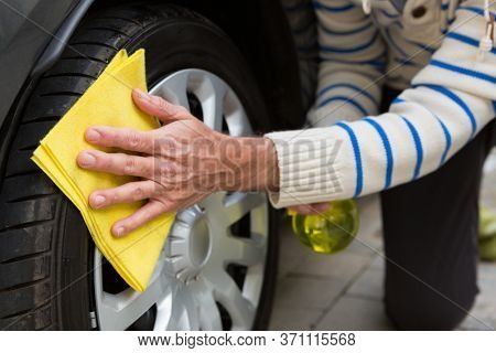 Male auto service staff cleaning a tyre with duster