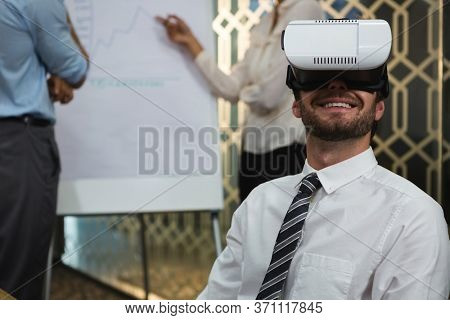 Businessman using virtual reality headset in conference room at office