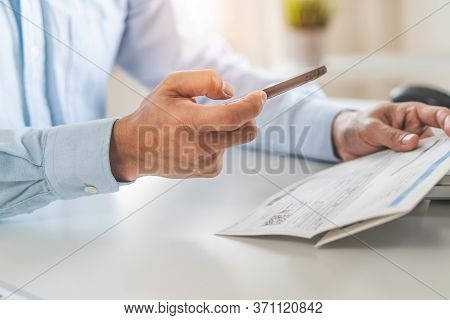 Close Up Hand Of Person Shopping In Mobile And Paying Via Internet Bank. View Of Person Paying Bills