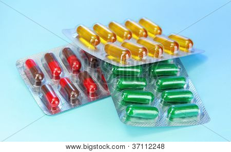 Capsules packed in blisters, on blue background