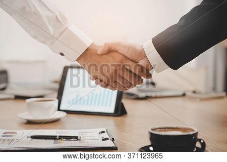 Hands Of Agent And Client Shaking Hands After Signed Contract .