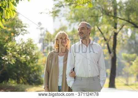 Elderly Couple Lifestyle Concept. Husband And Wife And Sit Walking In The Park.