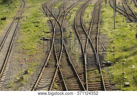Old Rusty But Functioning Empty Railroad Tracks Without Trains. Grass Grows On Rails.