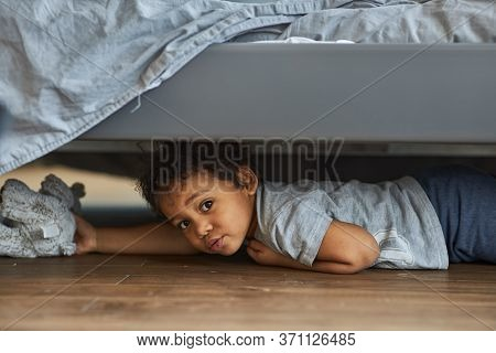 Family At Home Concept, Boy Playing Hide And Seek. Cute Afro Boy Peeking Out From Under The Bed.