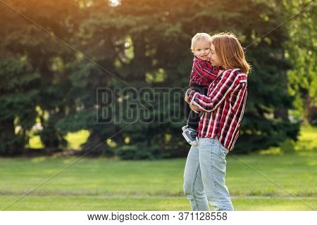 Happy Young Mother Is Playing With  Her Baby In A Park On A Green Lawn.concept Of A Happy Family. Mo