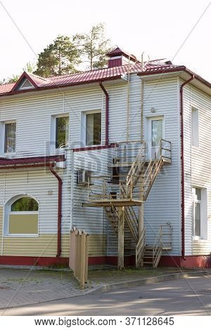 Fire Emergency Escape Ladder, External Emergency Exit With A Staircase Behind A Roadside Two-story W
