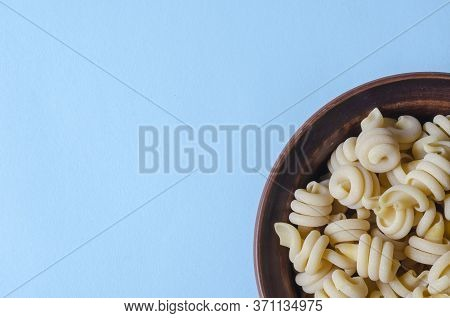 Serving Uncooked Insalatonde Pasta In A Bowl On A Light Blue Background. Ingredients Of Traditional