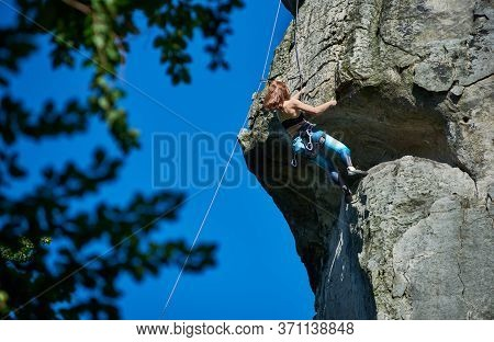 Brave Lady Alpinist In Sportswear Climbing Extremely Vertical Rock Under Beautiful Blue Sky. Woman M